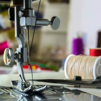 foot sewing machine with needle and thread in the background spools with colored threads